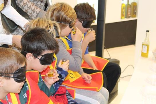 Los niños catan con los ojos vendados distintas variedades de aceite de oliva / Juan C. Morales